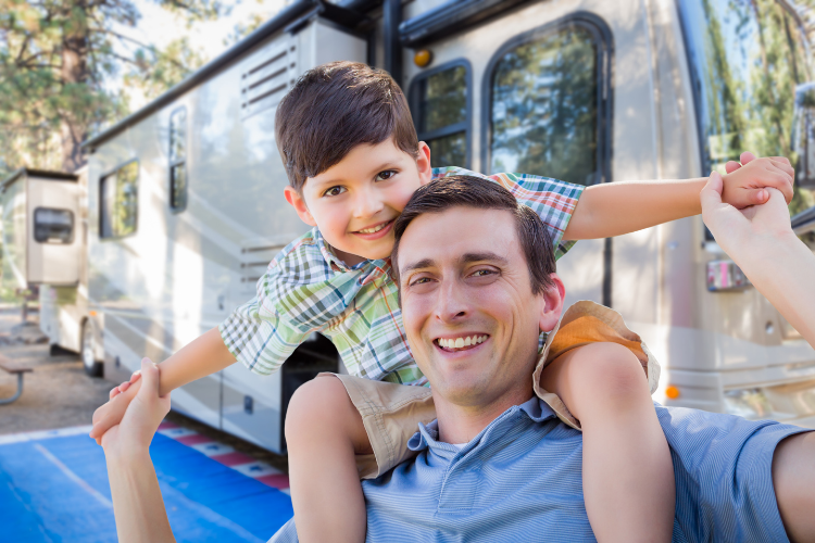 dad and son standing by a class a rv